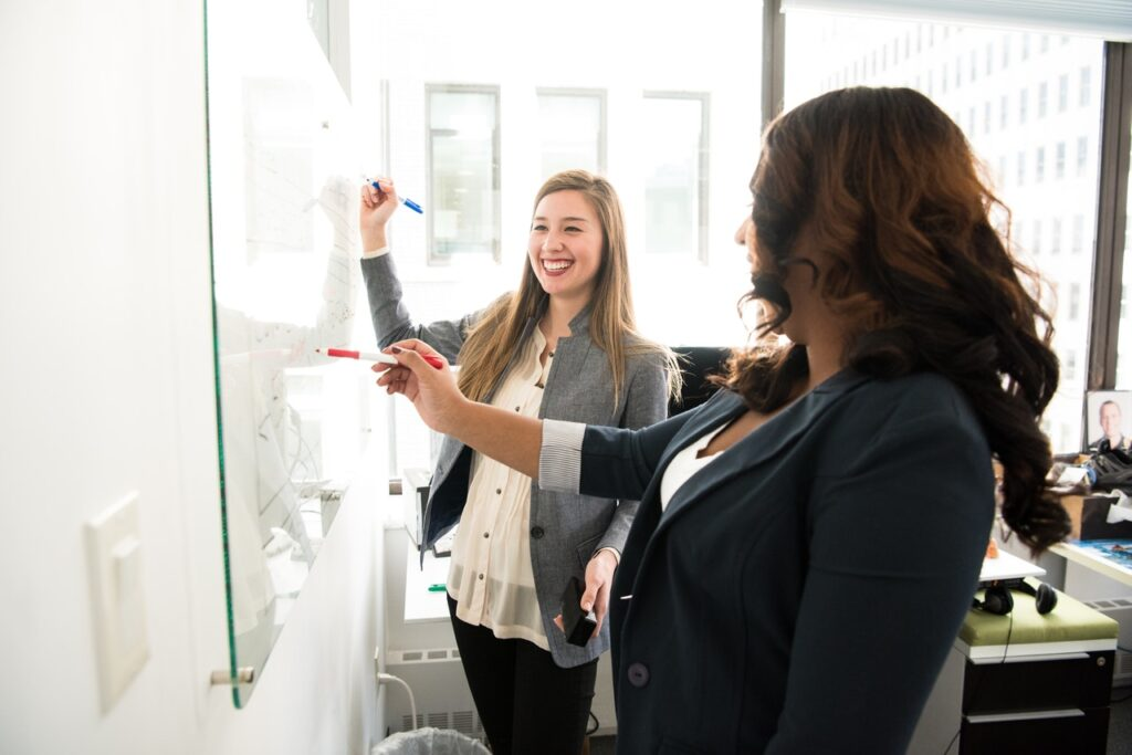 two-women-in-front-of-dry-erase-board-1181533 (1)