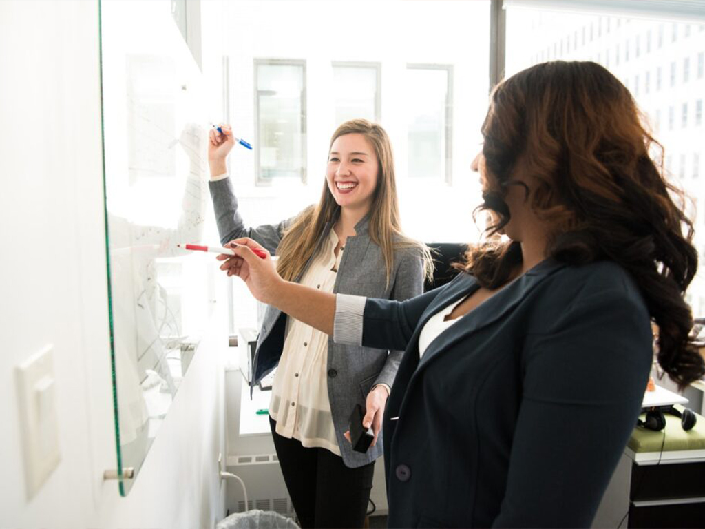 two-women-in-front-of-dry-erase-board
